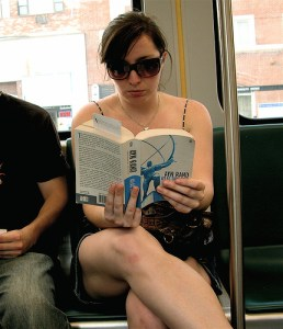 Young woman reading Atlas Shrugged on a subway