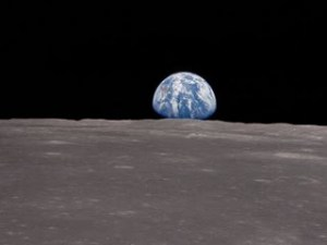 Earth rises above the horizon of the Moon before the crew of Apollo XI
