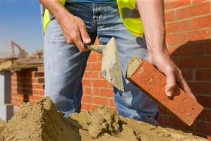 648-05549394 © Masterfile Royalty-Free Model Release: Yes Property Release: Yes Close up of bricklayer applying mortar to brick with trowel