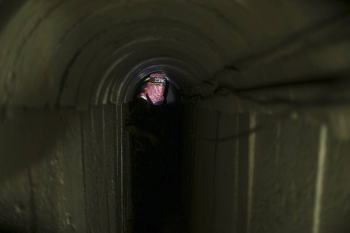 A Palestinian fighter from the Izz el-Deen al-Qassam Brigades, the armed wing of the Hamas movement, stands inside an underground tunnel in Gaza August 18, 2014. A rare tour that Hamas granted to a Reuters reporter, photographer and cameraman appeared to be an attempt to dispute Israel's claim that it had demolished all of the Islamist group's border infiltration tunnels in the Gaza war. Picture taken August 18, 2014. REUTERS/Mohammed Salem