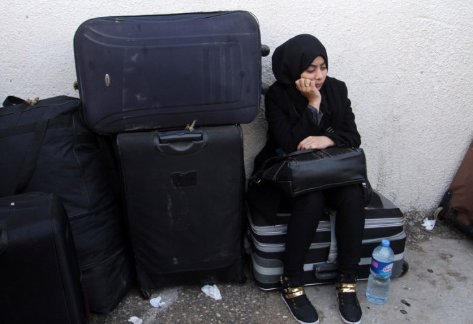 Palestinians wait for permission to enter Egypt at the Rafah border crossing in the southern Gaza Strip, on December 3, 2015. Egypt is due to re-open its Rafah border crossing with the Palestinian coastal enclave for two days. Photo by Abed Rahim Khatib