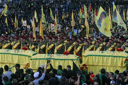 FILE - In this Tuesday, Oct. 27, 2015 file photo, relatives and comrades pray as they surround the Hezbollah flag-draped coffins of Shiite fighters who were killed in Syria, during a rally to mark the 13th day of the Shiite mourning period of Muharram, in Nabatiyeh, Lebanon. At tightly guarded facilities in south Lebanon, men as young as 17 undergo intensive training on how to use automatic rifles and heavy machine guns before being shipped off to Syria to fight alongside President Bashar Assad's forces. The training is part of a massive Hezbollah recruitment effort to make up for its human losses in Syria's war, now approaching the death toll incurred by the group during 18 years of fighting Israeli occupation.(AP Photo/Mohammed Zaatari, File)