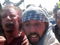 This video frame grab image taken from Libyan TV, purports to show former Libyan leader Moammar Gadhafi alive and surrounded by revolutionary fighters in Libya, Thursday Oct. 20, 2011. Arab satellite TV stations have broadcast the video showing Gadhafi captured alive by revolutionary forces. The video shows a wounded Gadhafi with a blood-soaked shirt and bloodied face leaning up against the hood of a truck and restrained by fighters. They then push him toward another car, as he shouts and struggles against them. (AP Photo/Libyan TV)