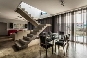 great-dining-room-with-glass-table-and-black-chair-and-concrete-staircase-and-glass-window-and-sleek-curtain