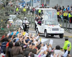 The Pope waves to crowds in Quito.