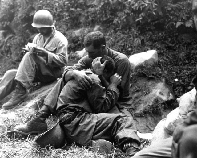English: A grief stricken American infantryman whose friend has been killed in action is comforted by another soldier. In the background a corpsman methodically fills out casualty tags, Haktong-ni area, Korea. August 28, 1950. Sfc. Al Chang. (Army) U.S. Army Korea Media Center official Korean War online video archive