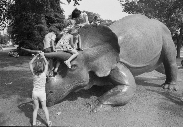 """""""Record Unit 95, Box 33, Folder 23""""; """"Six children play on the sculpture """"Uncle Beazley,"""" the 25 foot long replica of a triceratops, placed on the Mall in front of the National Museum of Natural History (NMNH)."""""""
