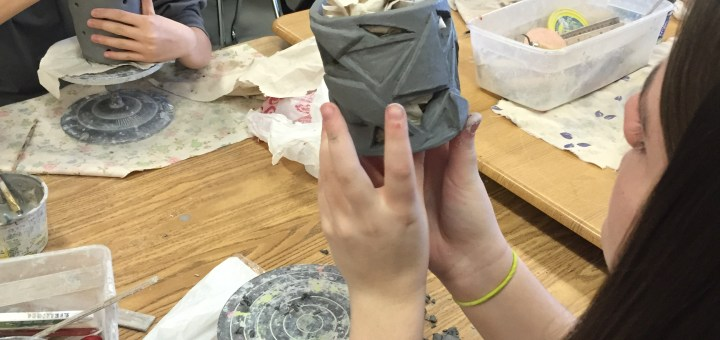 ZMS student Kristen Hohman displays the detail on a sculpted container she made as classmates Sophia Phan (from left), Phoebe Bailey and Brittany Jones work on their projects. (Submitted photo)