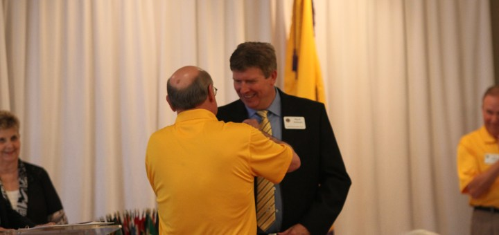 Zionsville Lions Club past president Mike Heffner (left) pins Mark Amman as the organization's new president April 14. (Photo by Keith Shepherd)