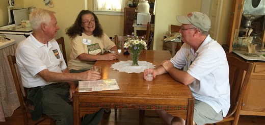 From left: Ralph Stacy, board member, Shelley Lakshamanan, board member, and Chris Garvye, president of Maplelawn Farmstead Inc. talk around a table in the farmhouse.