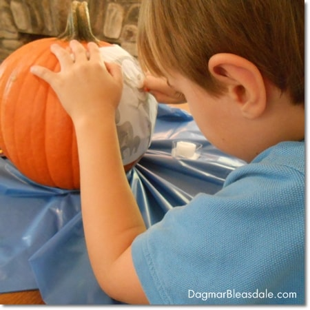 boy using Pumpkin Masters tool to trace design on pumpkin