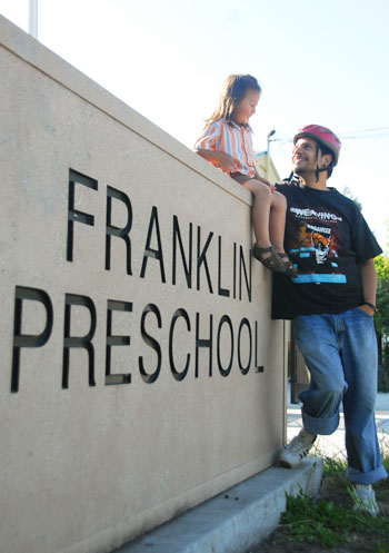 Pablo Paredes and his son pose at Franklin Preschool. The Board of Education voted to continue funding certain preschools.