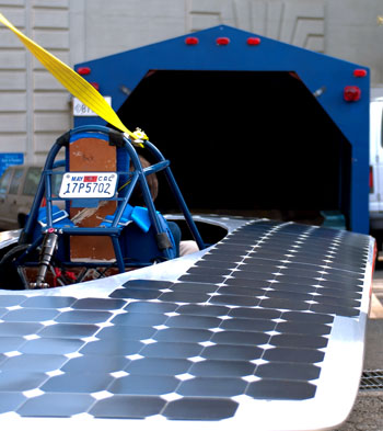 The solar vehicle built by CalSol, UC Berkeley's Solar Vehicle team, sits behind an open trailer.