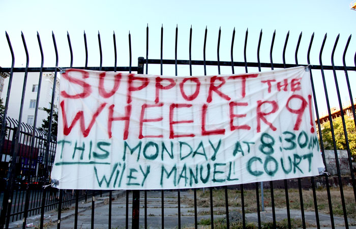 """A sign in support of the """"Wheeler 9"""" hanging on the fence around the vacant lot on the corner of Telegraph Avenue and Haste Street."""