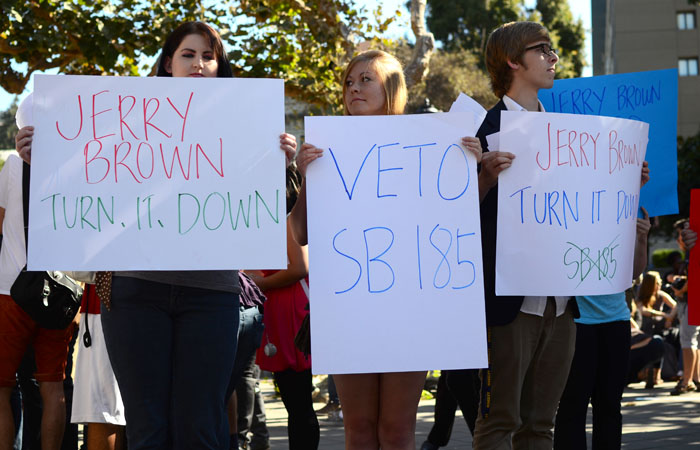 Participants at the Increase Diversity Bake Sale held signs urging Governor Jerry Brown to veto SB 185.