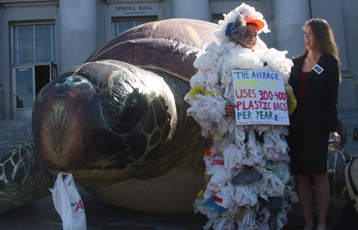 Members of CALPIRG, one of whom is covered in plastic bags, stand in front of a giant inflatable turtle on the steps of Sproul Hall.