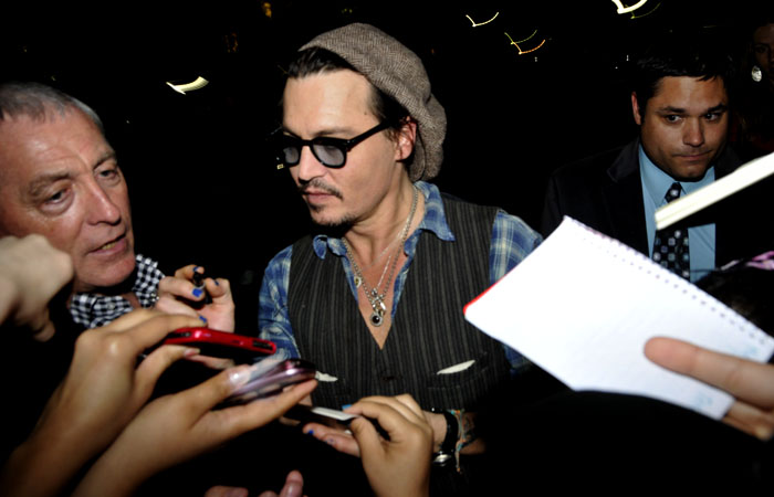 Actor Johnny Depp greets his fans and signs autographs as he leaves Wheeler Hall Monday night.