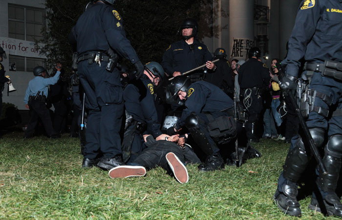 Police pin a protester to the ground.