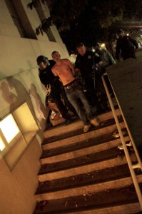 A shirtless protester is led away by police.