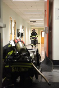 Firefighters place large fans at one of the entrances of Dwinelle Hall after a fire broke out in a bathroom trash can.