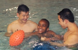 Brenzan Kim and Nick Chien, both students at UC Berkeley, work with a participant in the SNAP program at the warm water pool.