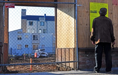 A passerby reads a sign posted on the facade of the burned down building at the corner of Haste Street and Telegraph Avenue. The sign outlines the proposal for the restaurant to reopen and operate out of tents.