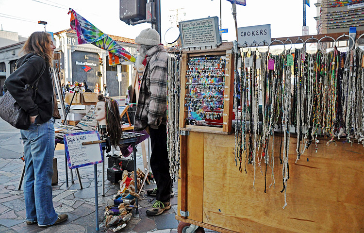 A street vendor works his stall on Telegraph Avenue.