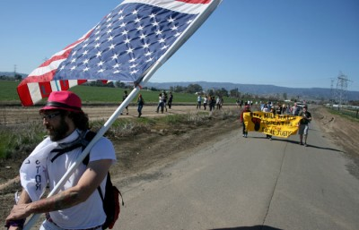 Wildabeast, who has come to the Bay Area from Occupy Boston carries an American flag on the 99 mile march from UC Berkeley to UC Davis. Anna Vignet/Senior Staff