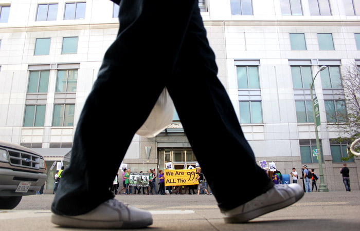 A passerby walks across the street from protest action in front of the UC Office of the President in Oakland.