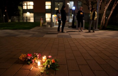 A group gathers near a handful of flowers and candles in the courtyard of Unit 2 after police left the scene.