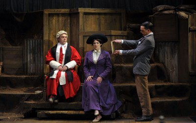Judge Darling (l. Kevin Clarke) watches as Noel Pemberton-Billing (r. Mark Anderson Phillips) presents Maud Allan (c. Madeline H.D. Brown) with a piece of harsh evidence against her.