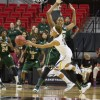 California guard Layshia Clarendon passes the ball around South Florida center Akila McDonald during the Golden Bears' 82-78 victory against the Bulls on Monday in the United Spirit Arena in Lubbock, Texas.