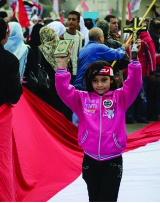 At a pro-Army protest this spring, a young girl carries the cross and the Qur'an to remind the protesters that the issue is an Egyptian issue, and not one of religion. She is walking on a massive Egyptian flag, which had ripped and is being sewn out of frame.