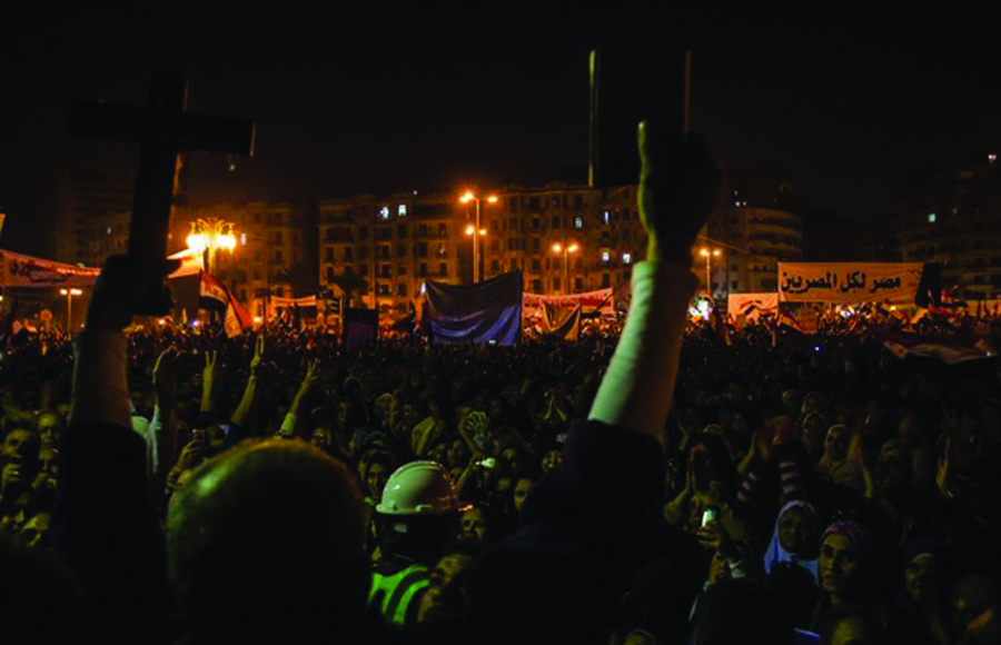 """At the first large-scale anti-Morsi protest (November 27, 2012) over 200,000 Egyptians gathered in Tahrir Square to protest President Morsi's overreaching his democratic powers. In the foreground a man from Alexandria holds a cross and Qur'an before the speakers' platform as a prominent reminder that their issues with the government are secular, but also an opportunity for unification. In the background the banner reads, """"Egypt for all Egyptians."""""""