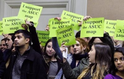Students hold up signs supporting that ASUC proposed student district map. Berkeley City Council discussed the two student districts at Tuesday's meeting.