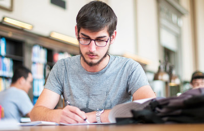 David Marn, a freshman at UC Berkeley from Slovenia, studies in Doe Library. Efforts to counter shrinking state funding of higher education have led to an increased dependence on out-of-state and international student tuition.