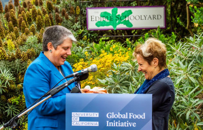 Alice Waters hands UC President Janet Napolitano a symbolic basket with eggs in it