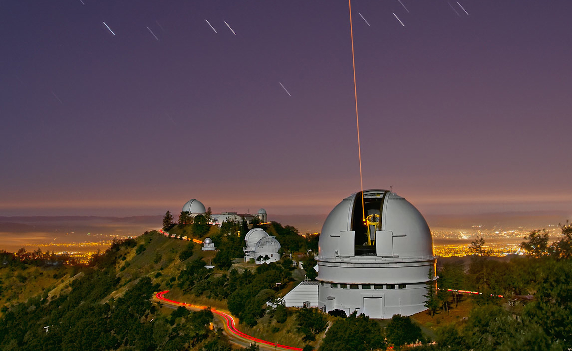 The laser beam used for adaptive optics exits the dome of Lick Observatory's Shane Telescope.  Graduate students have the opportunity to conduct research at Lick using such resources.