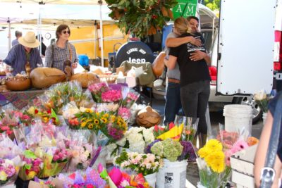 A grower and a customer hug at one of the most popular flower shops in the Market.