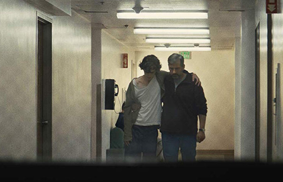 A young man and an older man walk in a room with their arms around each other.