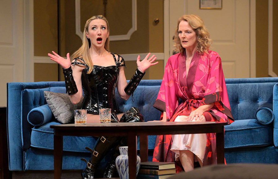 Two women sit on a blue couch, the on on the left is dressed in revealing black leather clothes with her hands in the air and a face of exlcamation. The woman next to her sits in shock, dressed in the pink robe.