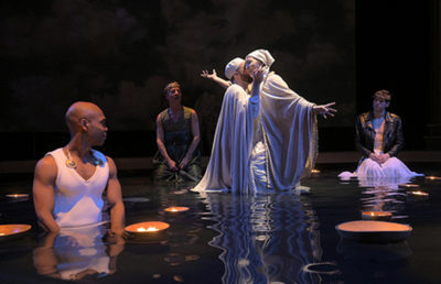 Two figures dressed in white robes stand in a pool while engaged in a yearning half embrace as two people sit at the edge of the pool behind them and watch. Another man stands in the foreground and looks back at the people embracing, also in the pool as the water is up to his waist.