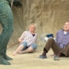 Two older people lie on the sand, in fear, crouching away from a green, large, threatening creature.