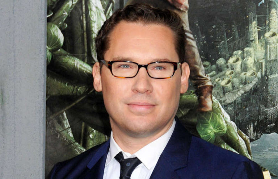 A man in a suit and glasses looks in the direction of the camera.
