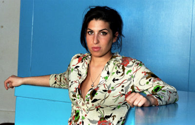 A woman in a floral long sleeve top sits in front on a blue wall and blue counter with her arms extended in relaxation.