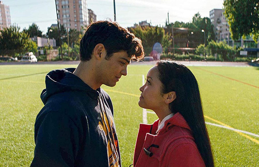 A teenage boy and teenage girl stand in a soccer field and look at each other.