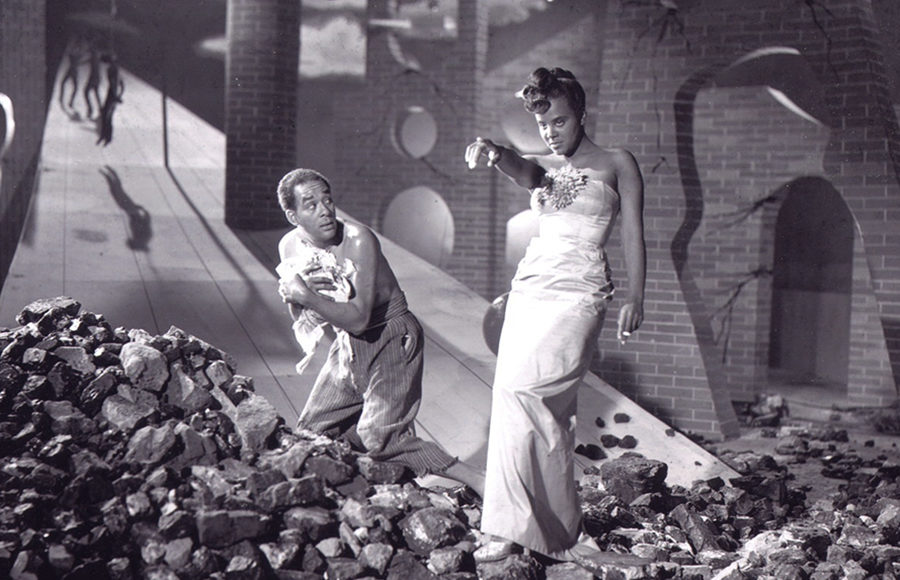 A woman in a fancy gown stands on a pile of rubble and brick as she points and stares into the distance as a man crouches behind her and looks at her with fear.