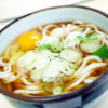 Checkered printed bowl of noodle soup topped with circular chopped onions and an uncooked egg rests on white surface.