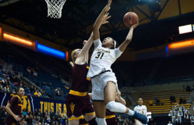 Basketball player jumps in the air with ball in hand, about to score a basket as an opponent tries to block her.