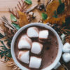 White cup of hot chocolate with six fluffy marshmallows floating on top, resting on a brown countertop with adornments of green and brown leaves around it.